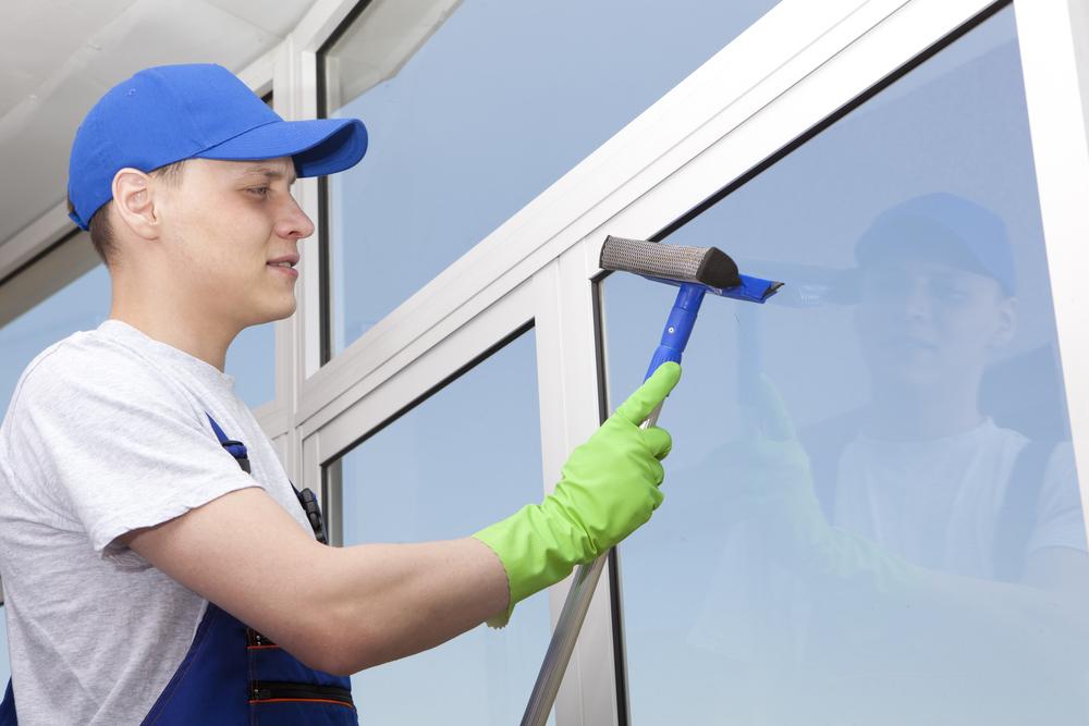 laveur de vitre avec une raclette qui nettoie une vitre